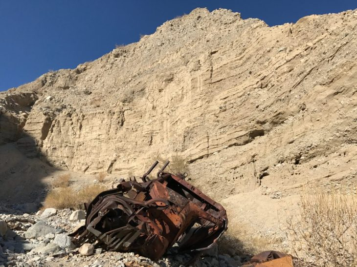 A remain of an old truck next to a canyon wall