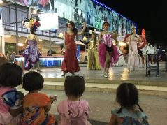 Kids watching a troop of drag performers advertising shows in the nearby venue